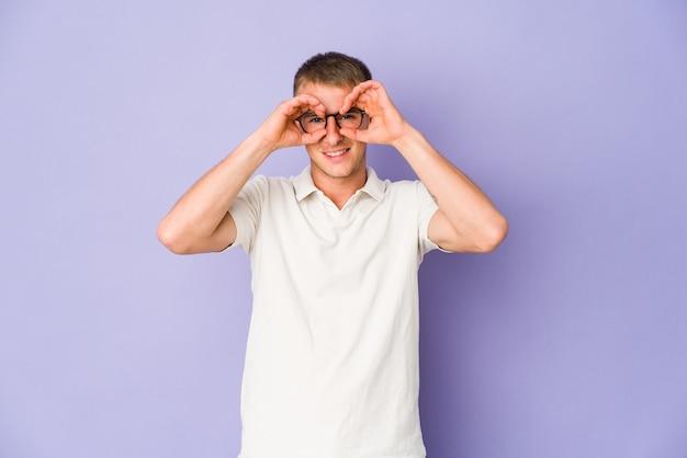 Jeune homme beau caucasien montrant un signe correct sur les yeux