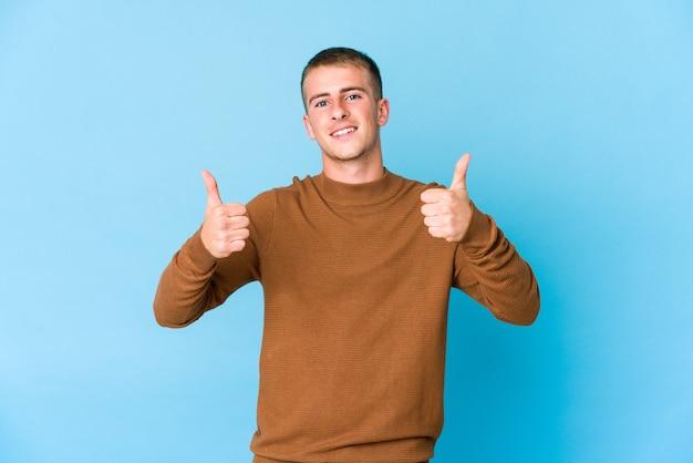 Jeune homme beau caucasien souriant et levant le pouce vers le haut