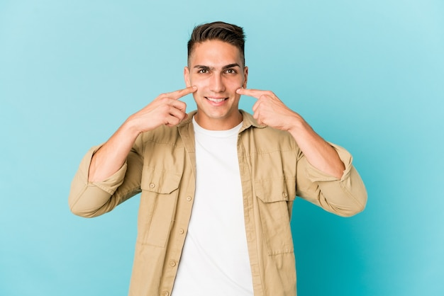 Jeune homme beau caucasien sourit isolé, pointant du doigt la bouche.