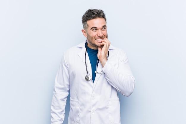 Jeune homme beau docteur se ronger les ongles, nerveux et très anxieux.