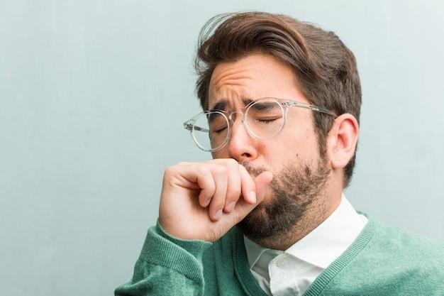 Jeune homme beau entrepreneur visage agrandi avec un mal de gorge, malade en raison d'un virus, fatigué et débordé