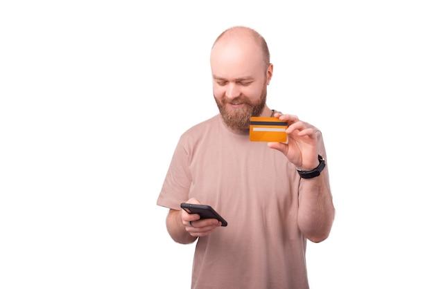 Jeune homme beau gai, achat en ligne avec carte de crédit au smartphone