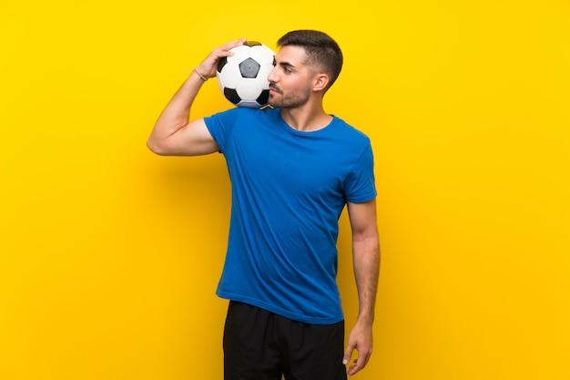 Jeune homme beau joueur de football sur mur jaune isolé