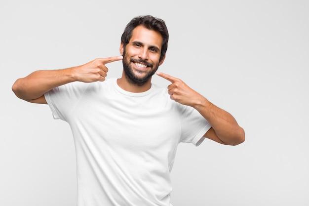 Jeune homme beau latin souriant avec confiance en montrant son large sourire, attitude positive, détendue et satisfaite