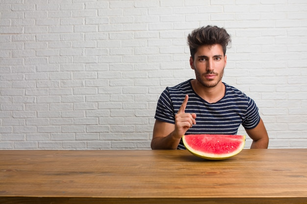 Jeune homme beau et naturel assis sur une table montrant le numéro un, symbole de comptage.