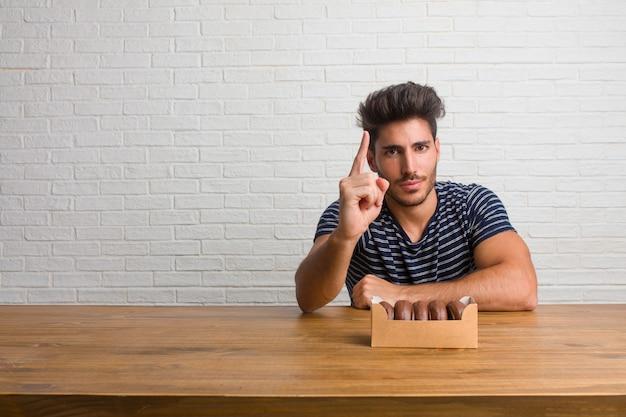 Jeune homme beau et naturel assis sur une table montrant le numéro un, symbole de comptage