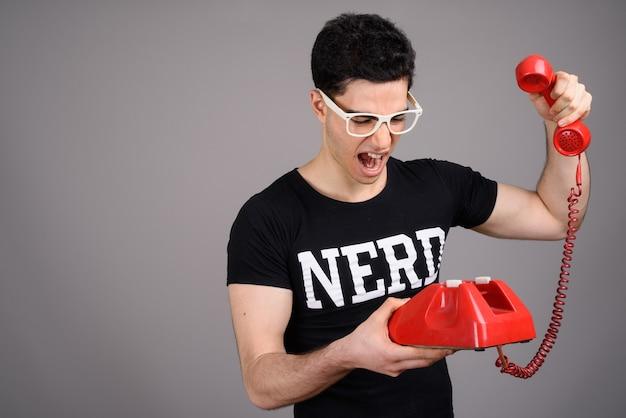 Jeune homme beau nerd avec des lunettes contre le gris