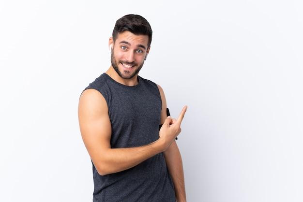 Jeune homme beau sport avec barbe sur blanc pointant vers le côté pour présenter un produit