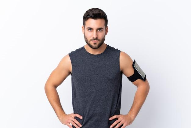 Jeune homme beau sport avec barbe sur blanc posant avec les bras à la hanche