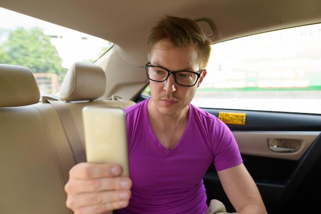 Jeune homme beau touriste à l'aide de téléphone sur le siège arrière de la voiture