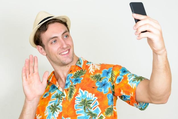 Jeune homme beau touriste prêt pour des vacances isolé