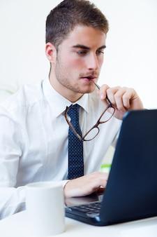 Jeune homme beau travaillant dans son bureau avec un ordinateur portable.