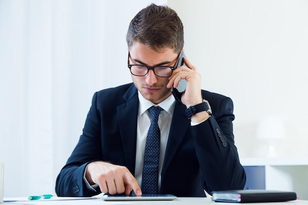 Jeune homme beau travaillant dans son bureau avec un téléphone mobile.