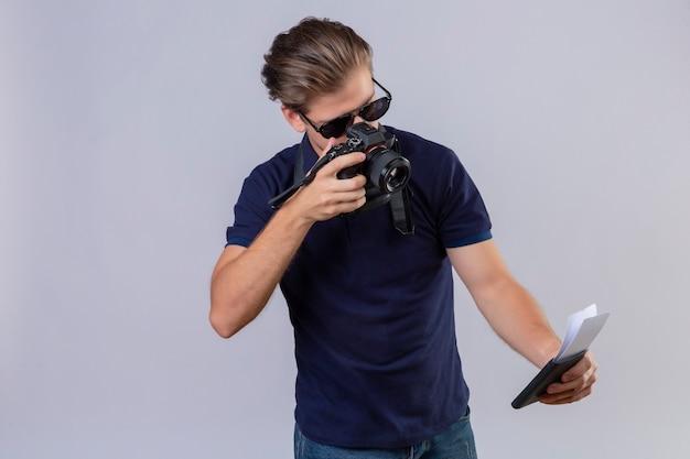 Jeune homme beau voyageur à l'aide de l'appareil photo en prenant des photos de ses billets debout sur fond blanc