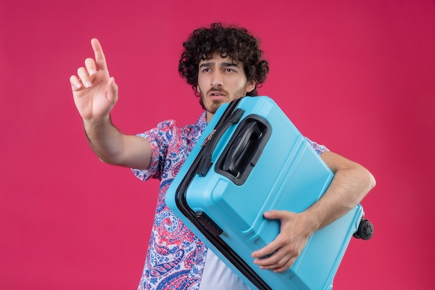 Jeune homme beau voyageur bouclé tenant valise et étirant la main sur un mur rose isolé