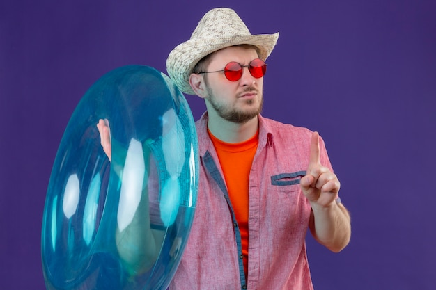Jeune homme beau voyageur en chapeau d'été avec anneau gonflable pointant le doigt vers le haut