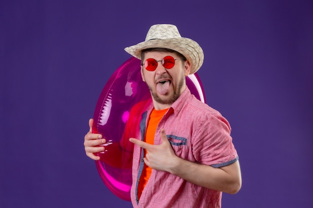 Jeune homme beau voyageur en chapeau d'été avec anneau gonflable