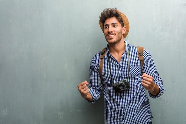 Jeune homme beau voyageur portant un chapeau de paille, un sac à dos et un appareil photo très heureux