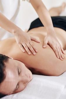 Jeune homme bénéficiant d'un massage du dos