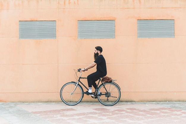Jeune homme à bicyclette devant le mur beige