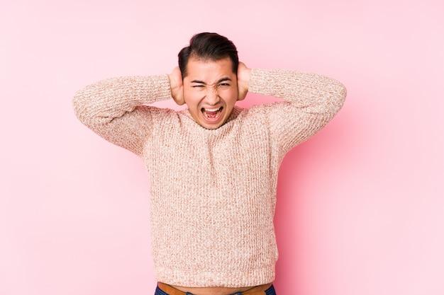 Jeune homme bien roulé posant en rose