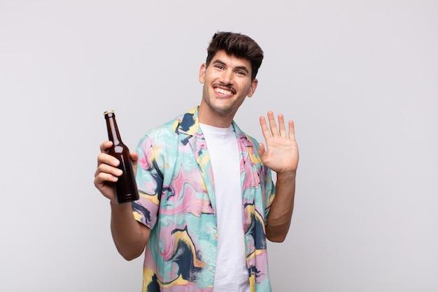 Jeune homme avec une bière souriant joyeusement et gaiement, en agitant la main, en vous accueillant et en vous saluant, ou en vous disant au revoir