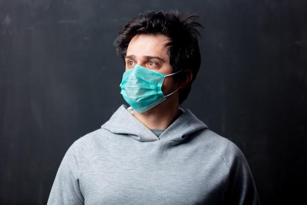 Jeune homme blanc en masque de protection sur fond sombre