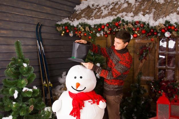 Jeune homme blanc en tenue d'hiver mettant un chapeau noir sur un bonhomme de neige d'intérieur, avec une écharpe rouge, dans une maison en bois entourée d'ornements de noël.