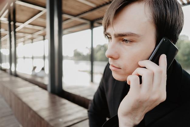 Jeune homme blanc tient un smartphone à la main.