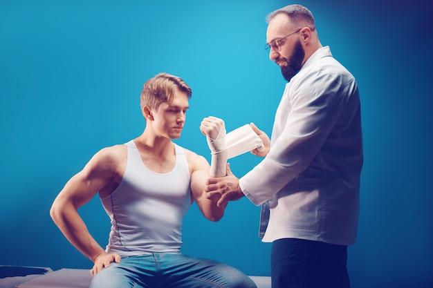 Jeune homme blessé à la main dans le cabinet du médecin le médecin fait un pansement au patient