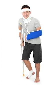 Un jeune homme blessé porte une écharpe et une béquille