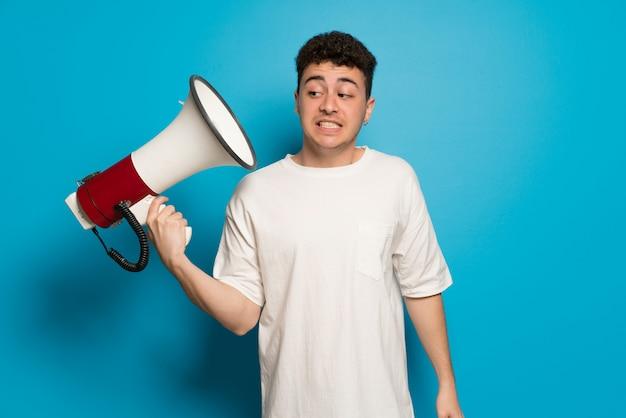 Jeune homme sur bleu prenant un mégaphone qui fait beaucoup de bruit