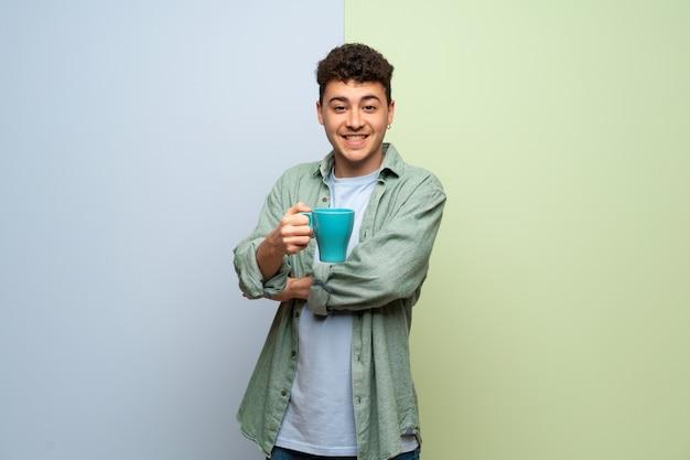 Jeune homme sur bleu et vert tenant une tasse de café