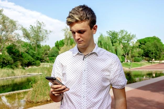 Jeune homme blond à l'aide d'un téléphone portable à l'extérieur