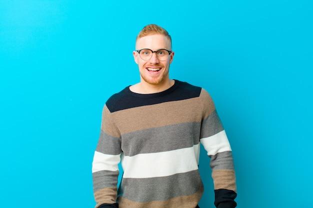 Jeune homme blond à l'air heureux et agréablement surpris, excité par une expression fascinée et choquée