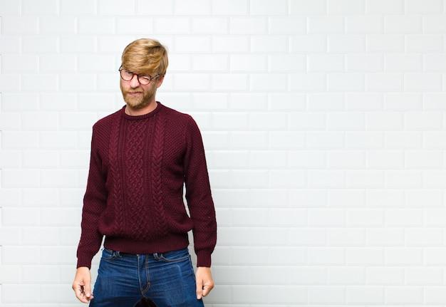 Jeune homme blond à l'air heureux et amical, souriant et un clin d'œil à vous avec une attitude positive contre le mur de carreaux vintage