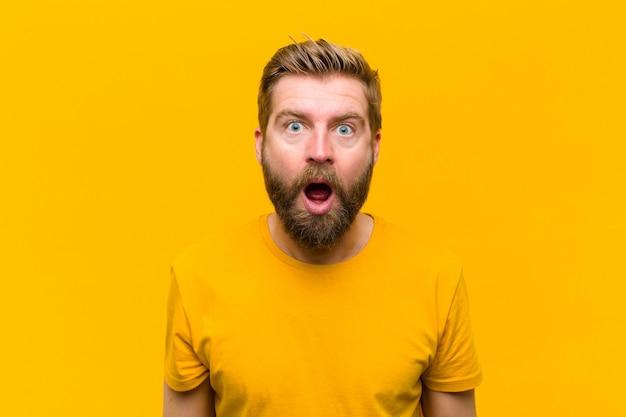 Jeune homme blond, l'air très choqué ou surpris, regardant avec la bouche ouverte disant: wow contre le mur orange