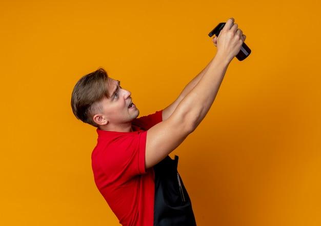 Jeune homme blond anxieux coiffeur en uniforme se tient sur le côté tenant le flacon pulvérisateur isolé sur l'espace orange avec copie espace