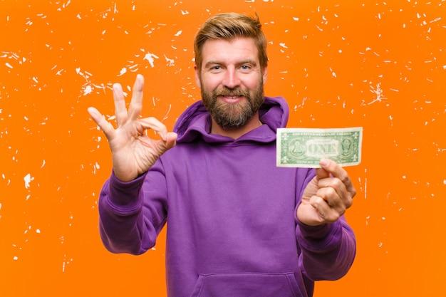 Jeune homme blond avec des billets d'un dollar ou des billets de banque portant un mur à capuchon violet endommagé orange