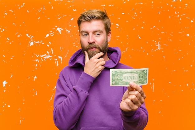 Jeune homme blond avec des billets d'un dollar ou des billets de banque portant un sweat à capuche violet