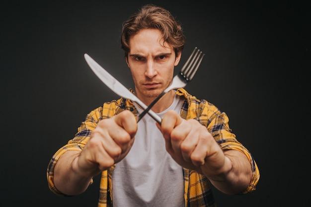 Jeune homme blond en chemise jaune sourit tout en tenant une fourchette et un couteau en arrêtant