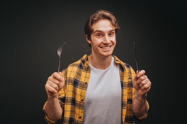 Jeune homme blond en chemise jaune sourit tout en tenant une fourchette et un couteau