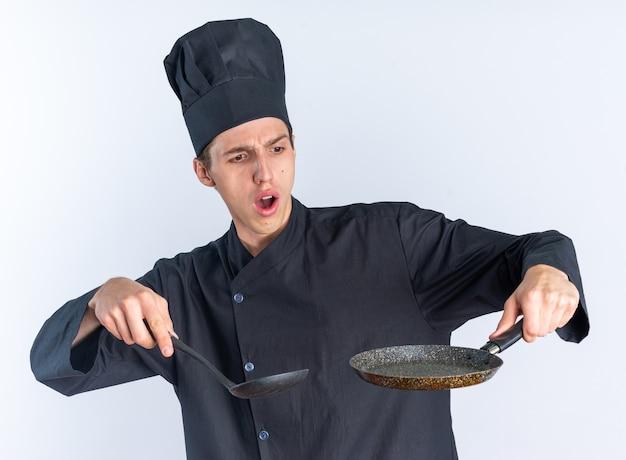 Jeune homme blond concerné cuisinier en uniforme de chef et casquette tenant une spatule et une poêle à frire regardant une poêle à frire isolée sur un mur blanc