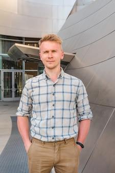 Un jeune homme blond dans une chemise pose dans le style d'affaires à walt disney concert hall à los angeles