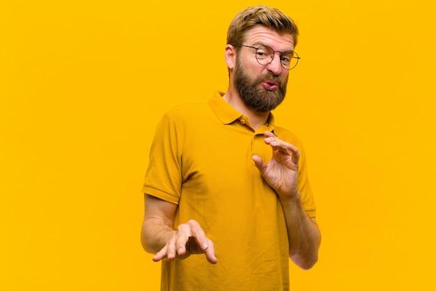 Jeune homme blond dégoûté et nauséeux, s'éloignant de quelque chose de méchant, puant ou puant, disant beurk sur le mur orange