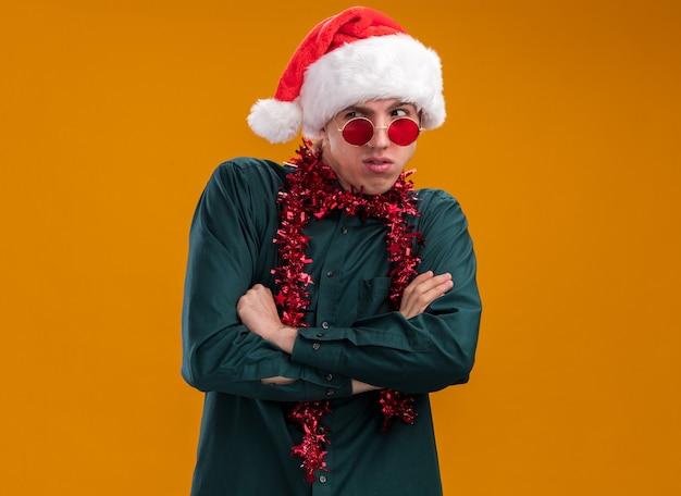 Jeune homme blond délicat portant un bonnet de noel et des lunettes avec une guirlande de guirlandes autour du cou, debout avec une posture fermée regardant le côté isolé sur fond orange avec espace de copie