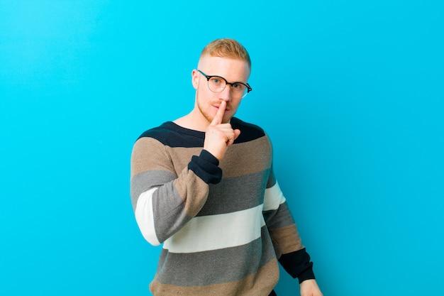 Jeune homme blond demandant le silence et la tranquillité, faisant des gestes avec le doigt devant la bouche, disant chut ou gardant un secret sur le bleu
