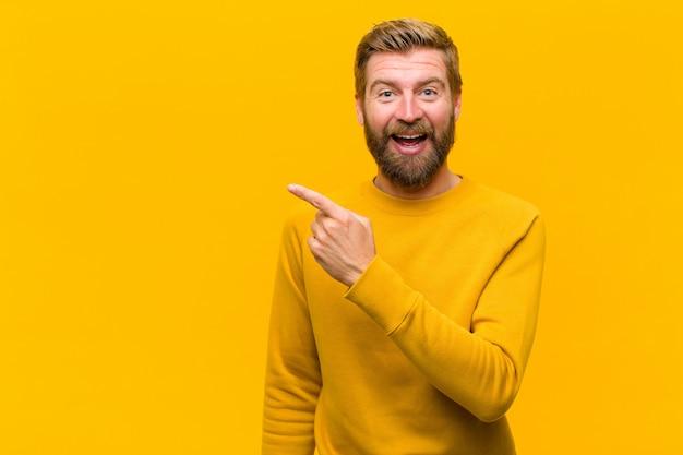 Jeune homme blond, excité et surpris, pointant du côté et vers le haut pour copier l'espace contre le mur orange