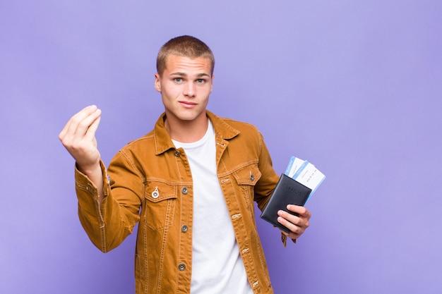 Jeune homme blond faisant capice ou geste d'argent