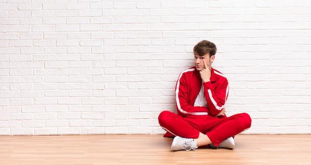 Jeune homme blond, gardant un œil sur vous, ne faisant pas confiance, regardant et restant vigilant et vigilant assis sur le sol